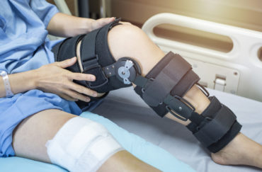 Asian woman patient with bandage compression knee brace support injury on the bed in nursing hospital.healthcare and medical support.