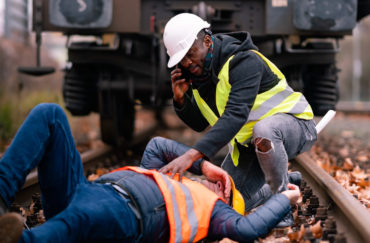 worker injured in an accident at work on the railway tracks. Coworker calling for help